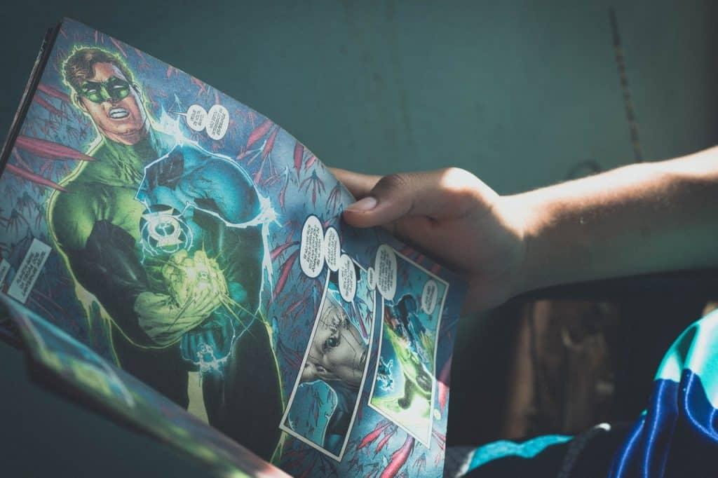 Um menino segurando uma revista de histórias em quadrinhos.