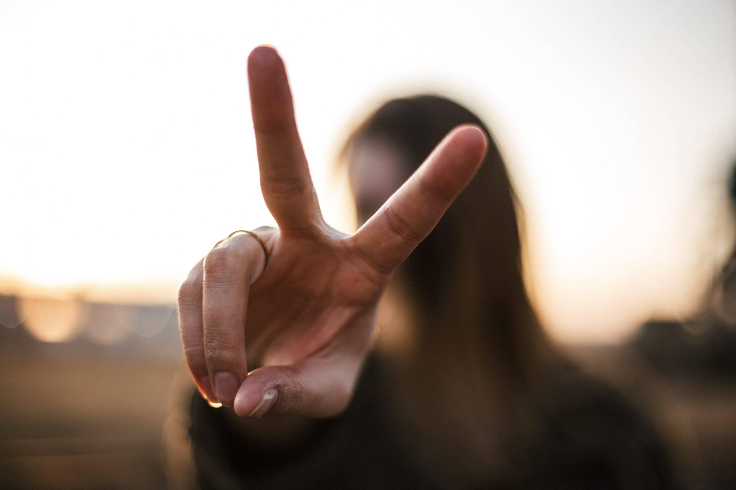 Moça fazendo o símbolo de paz e amor com as mãos.