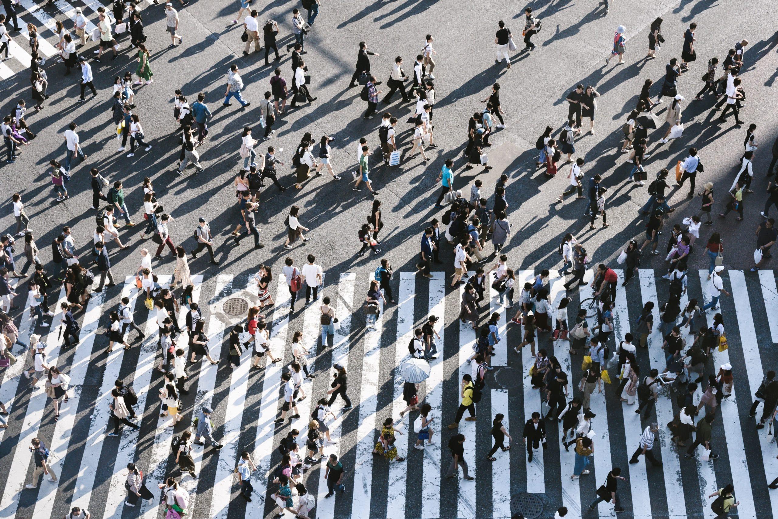 Avenida com faixa de pedestre e pessoas atravessando