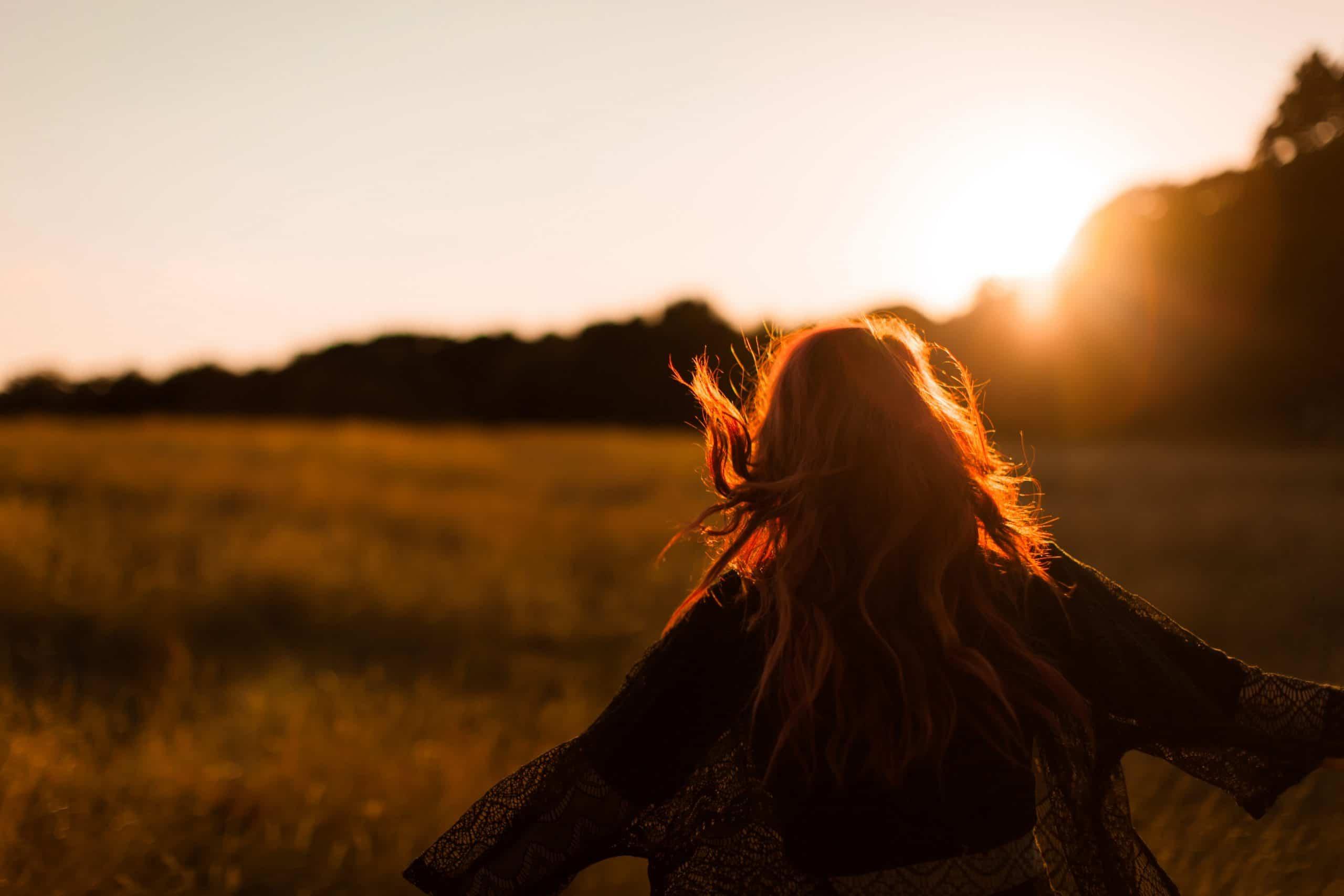Mulher de costas iluminada pelo sol