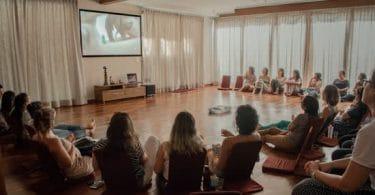 Sala com mulheres sentadas assistindo parto no telão