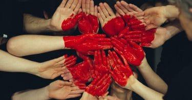 Mãos unidas pintadas de vermelho formando um coração