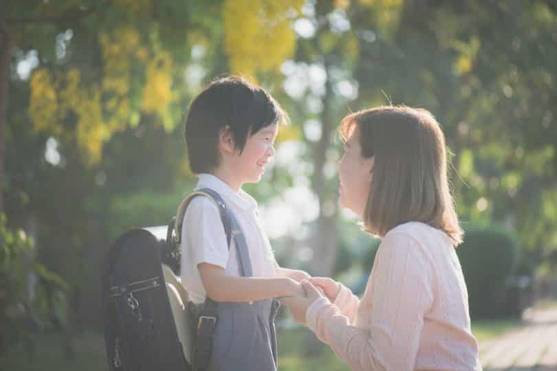 Mãe e filho de perfil se olhando e sorrindo um para o outro iluminados pelo sol