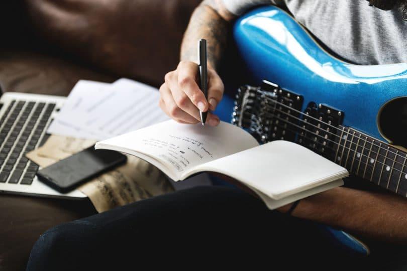 Homem com guitarra azul, escrevendo em um caderno