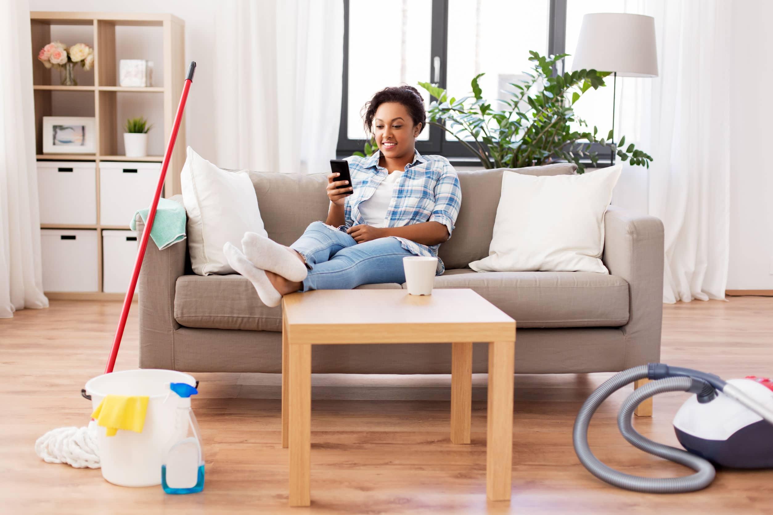 Mulher sentada no sofá olhando o celular.