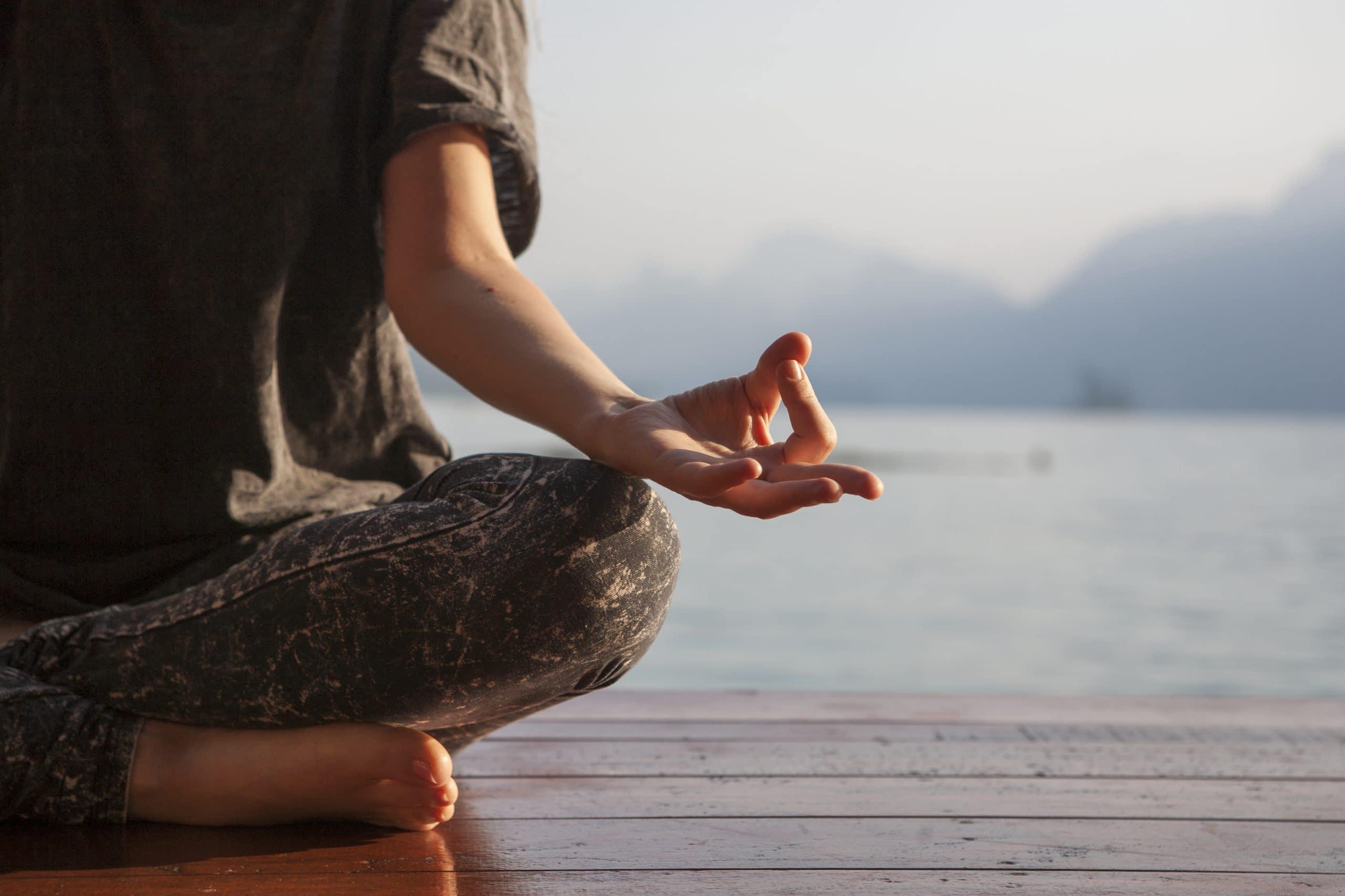Metade do corpo de uma mulher meditando.