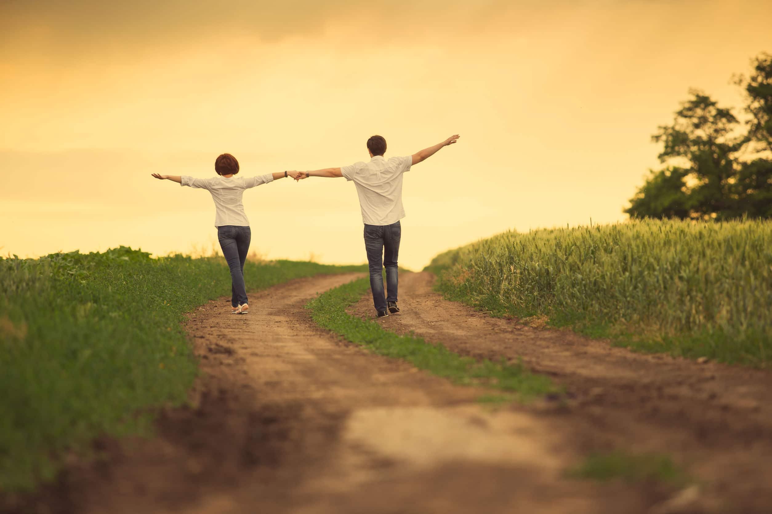 Casal andando de mãos dadas com braços abertos.