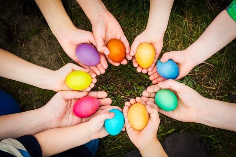 Mãos brancas segurando ovos coloridos.