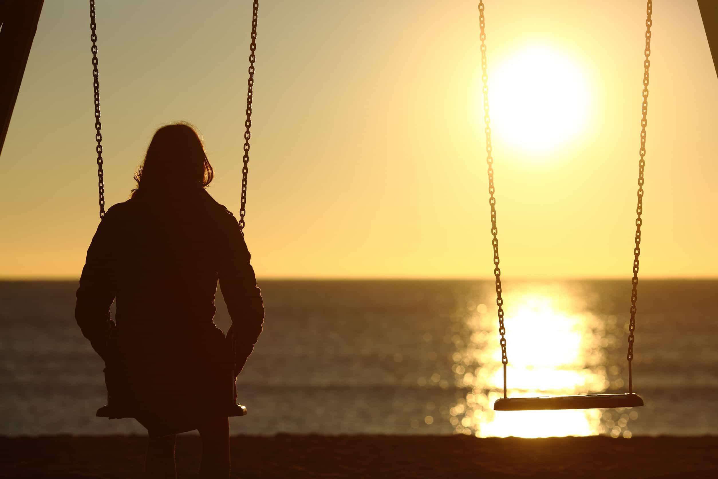Mulher sentada em um balanço ao lado de outro vazio.