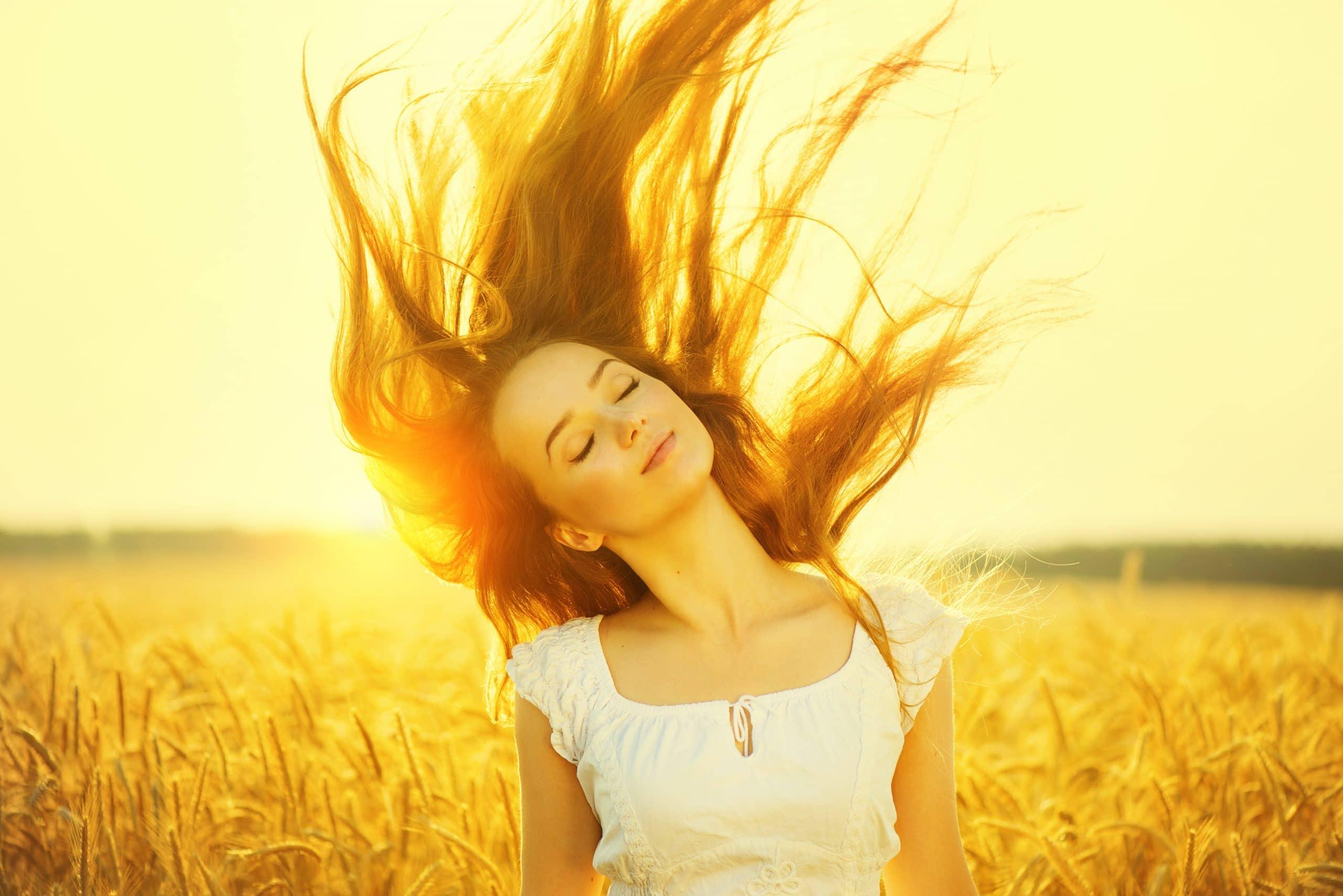 Mulher em um campo com os cabelos ao vento.
