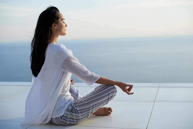 Mulher praticando ioga ao pôr do sol com vista para o mar ao fundo.