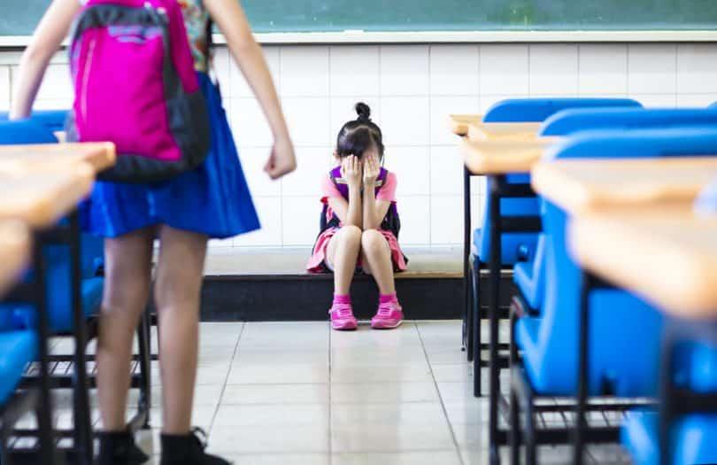 Menina em pé na sala de aula fazendo bullying com sua colega de classe, que chora no chão, sentada.