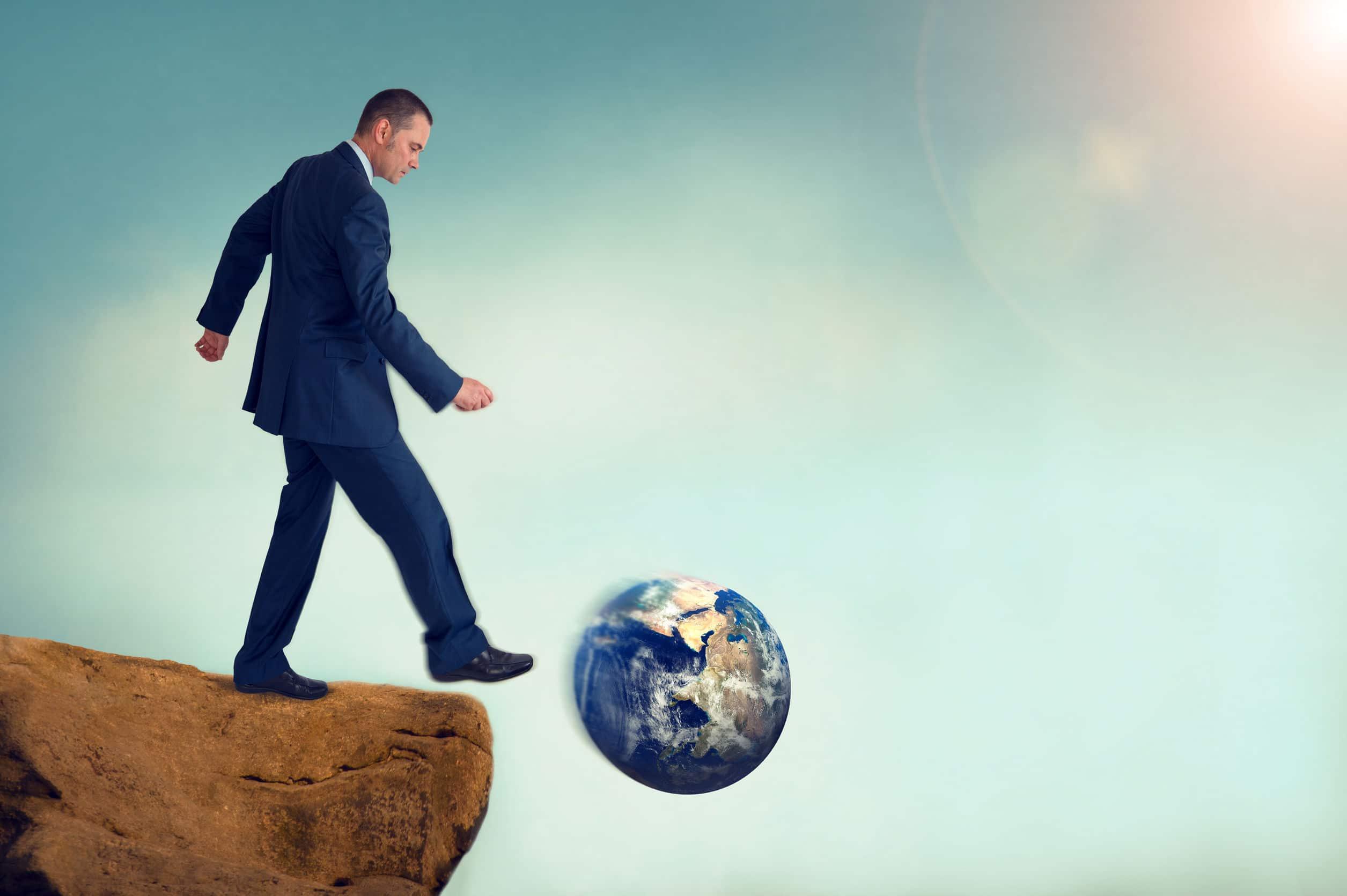 Homem executivo chutando a figura do planeta Terra.