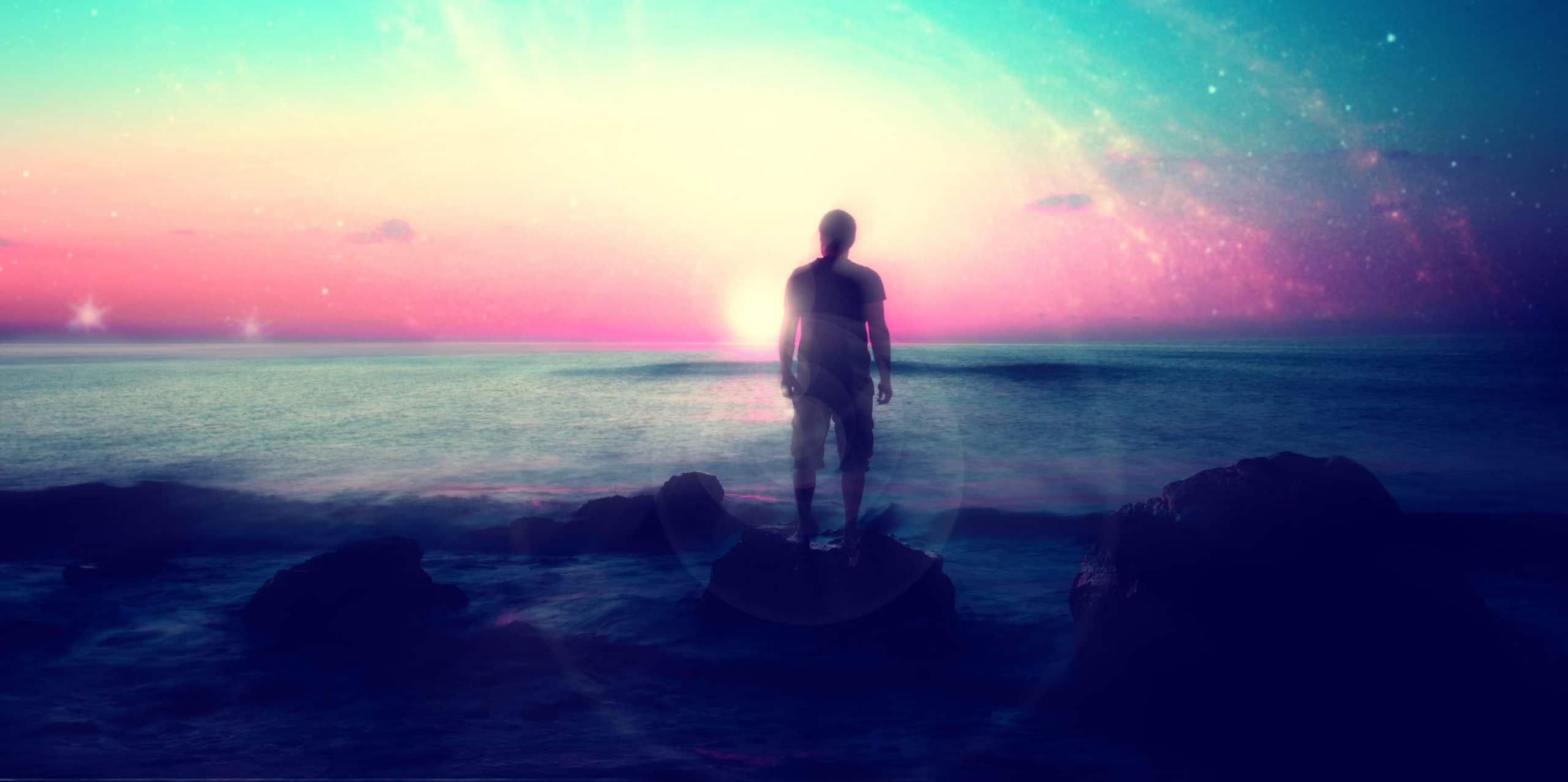 Homem parado diante de lago.