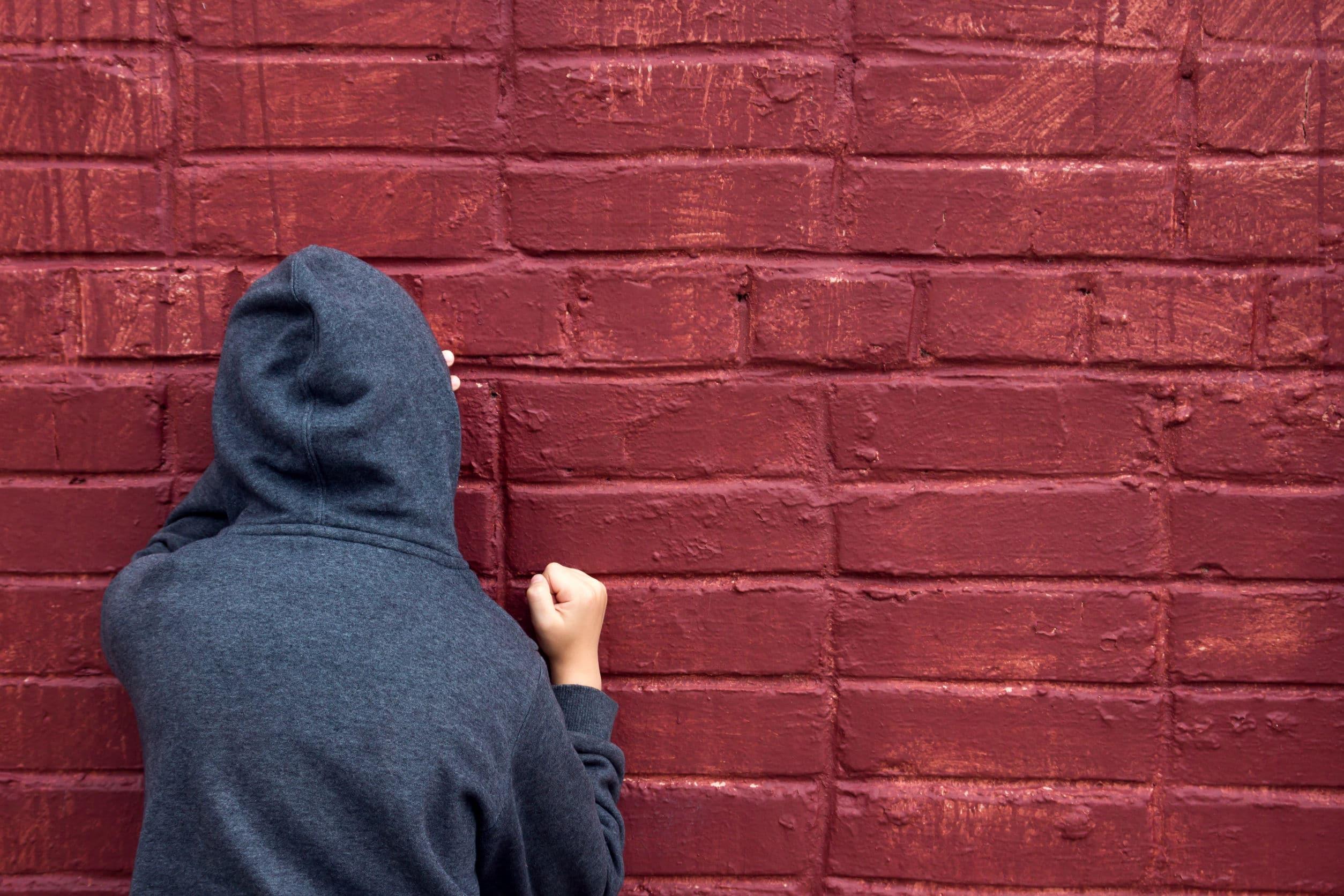 Homem de capuz com rosto apoiado na parede.