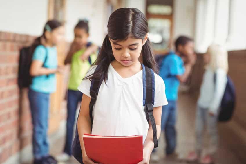 Menina andando pelo corredor da escola enquanto sofre bullying de seus colegas.