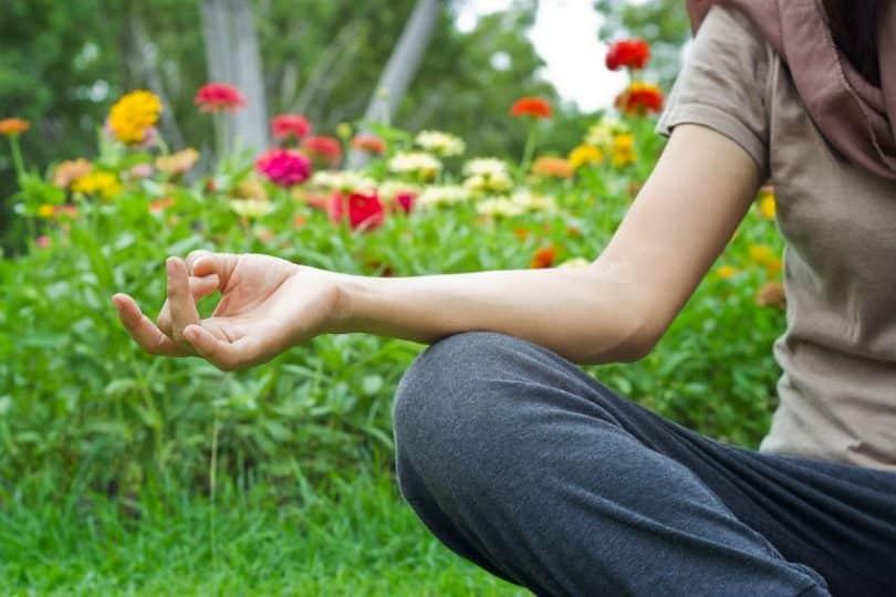 Pessoa sentada na grama, meditando, cercada por flores