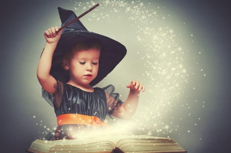 bruxinha alegre com uma varinha mágica e um livro brilhante