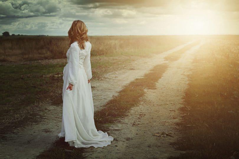 Mulher de costas olhando estrada com sol reluzindo
