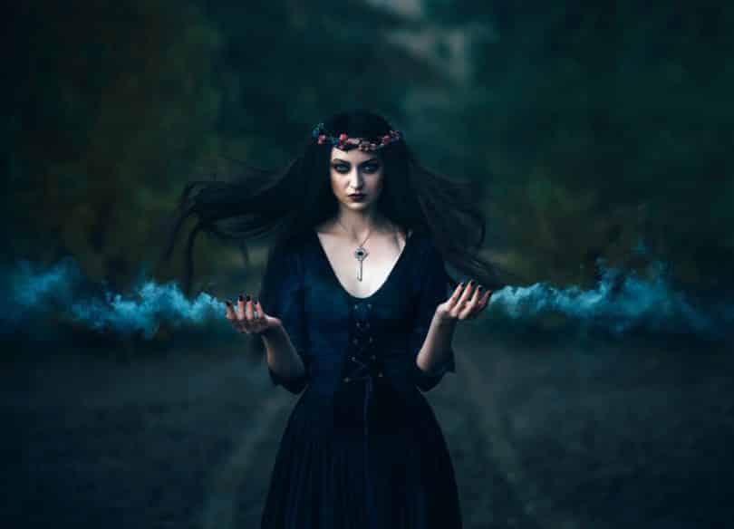 Mulher com roupas de época e coroa de flores olhando para frente enquanto lança fumaça de suas mãos.