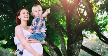 Mão grávida com filho mais velho no colo