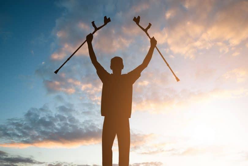 Homem em pé segurando muletas para cima.