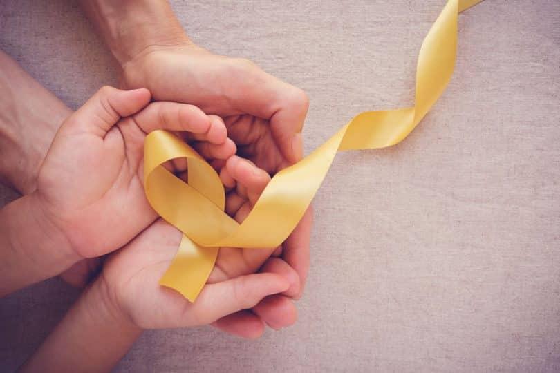 Mãos unidas com fita amarela em formato de luta contra à depressão