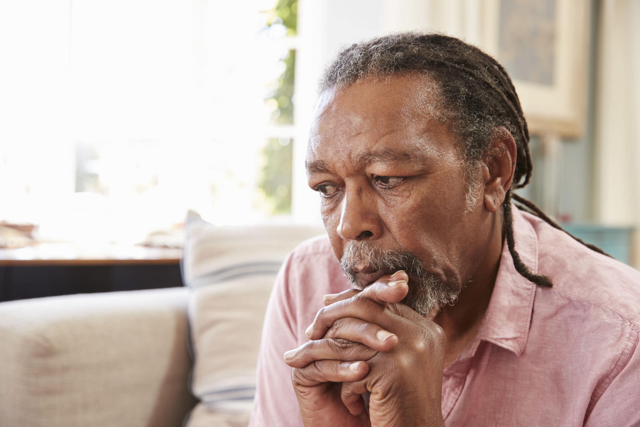 Homem de pele negra com expressão de pensativo.