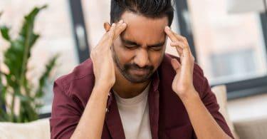 Homem com mãos na cabeça e olhos fechados com dor