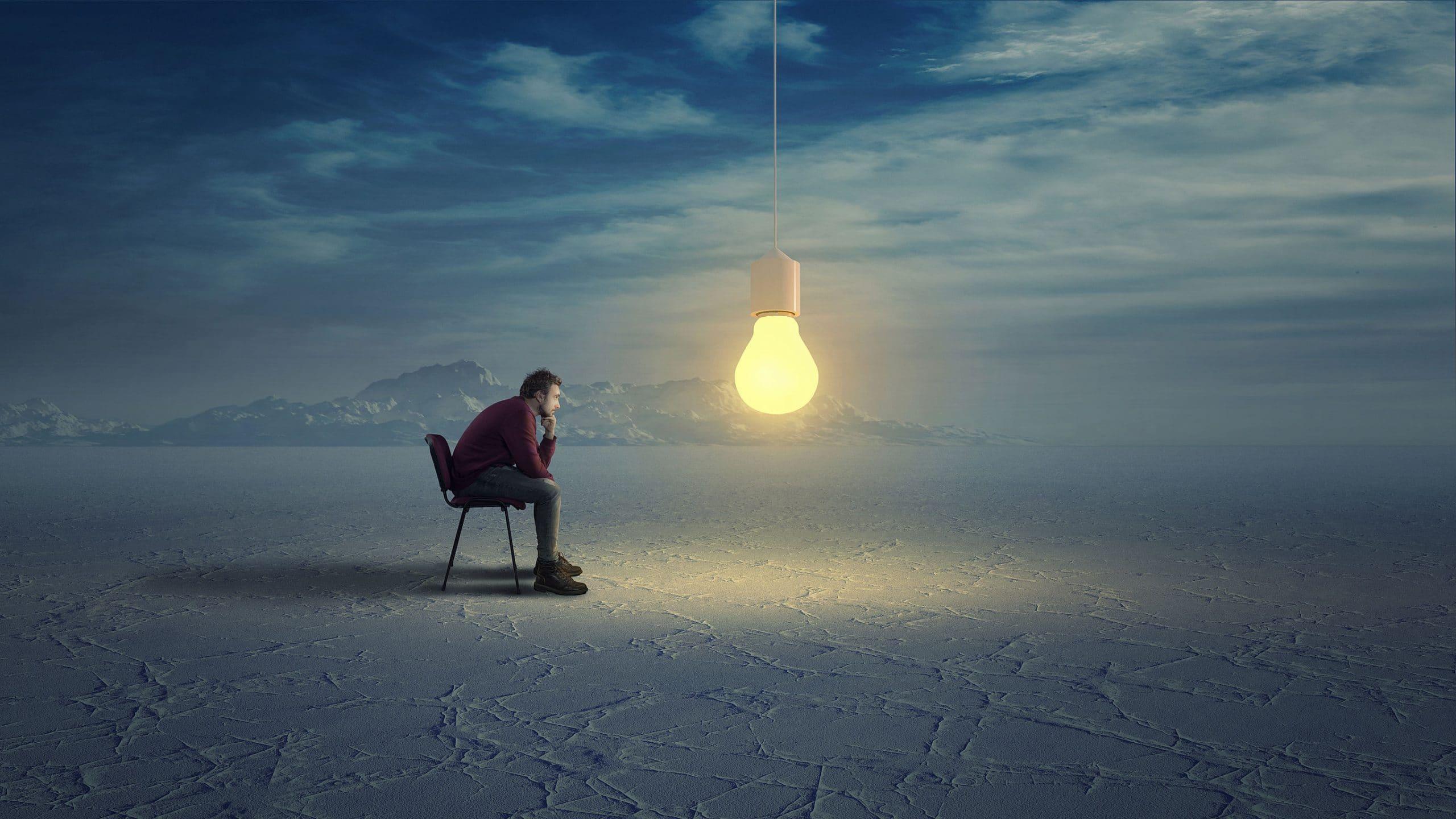 Homem sentado em uma cadeira de frente para uma lâmpada.