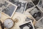 Diversas fotografias espalhadas em uma mesa. Um relógio também está no meio delas