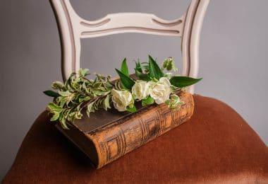 Livro fechado em cima de uma cadeira com rosas em cima.