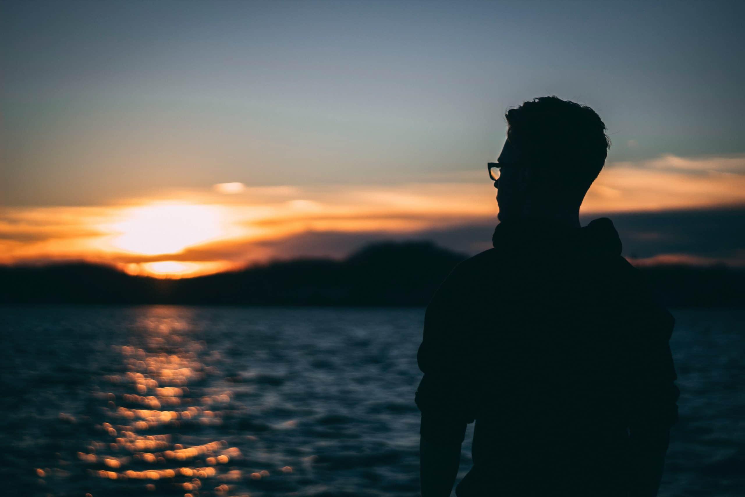 Silhueta de homem de costas olhando para o sol ao fundo