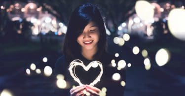 Garota segurando arco de luz em forma de coração.