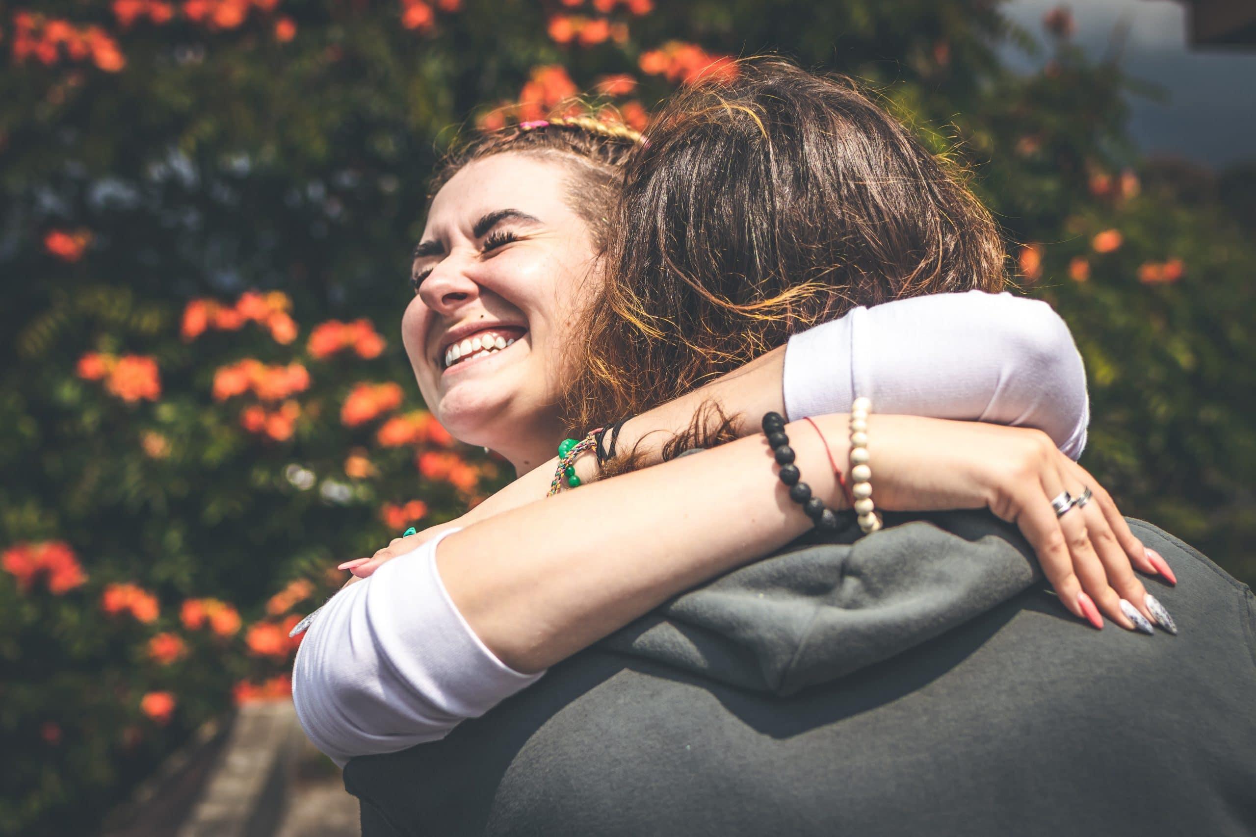Garota sorrindo abraçando outra