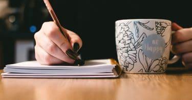 Mão escrevendo com xícara ao lado