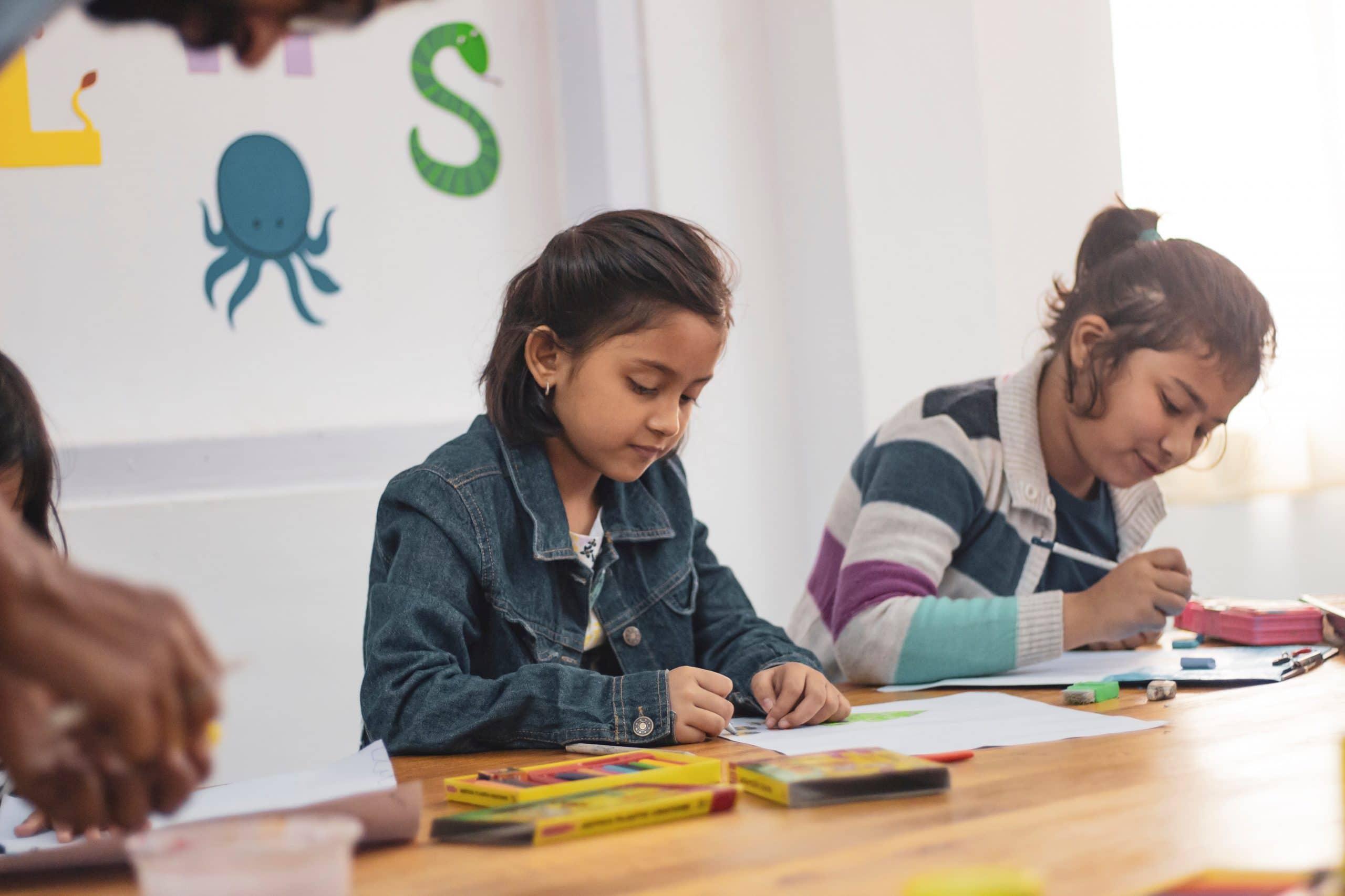 Alunas em sala de aula desenhando
