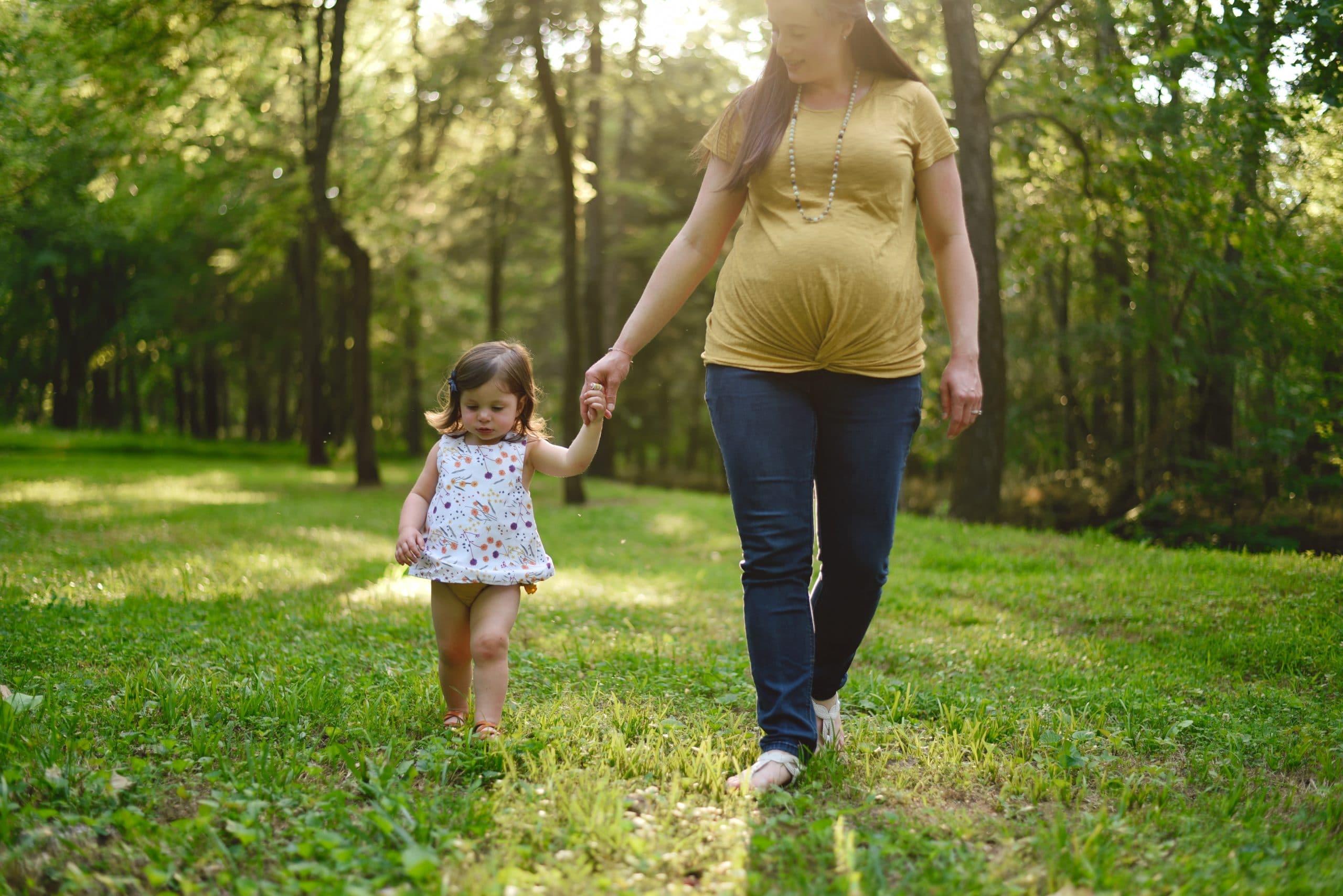 Mão grávida caminhando de mãos dadas com filha pequena