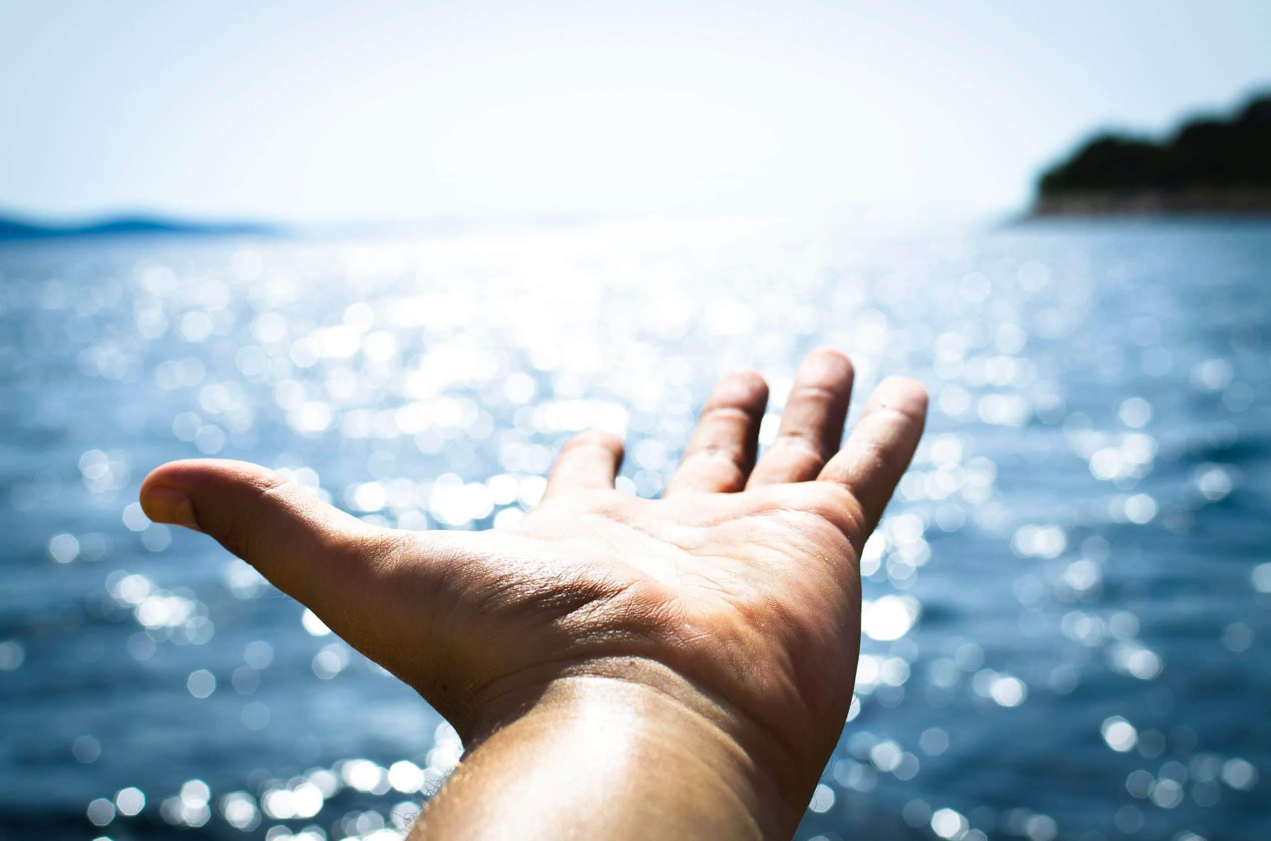 Mão para cima com mar ao fundo