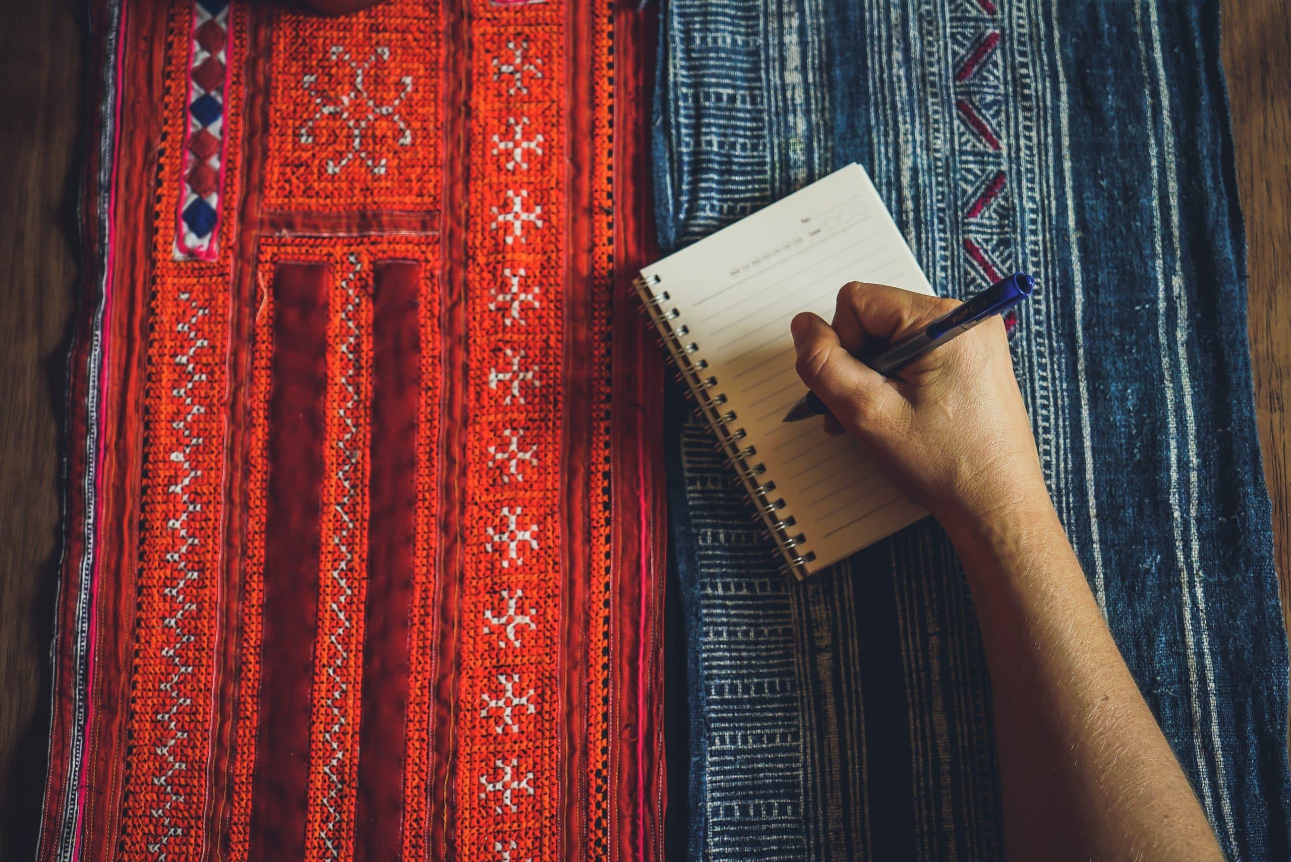 Mão segurando uma caneta sobre bloco de notas.