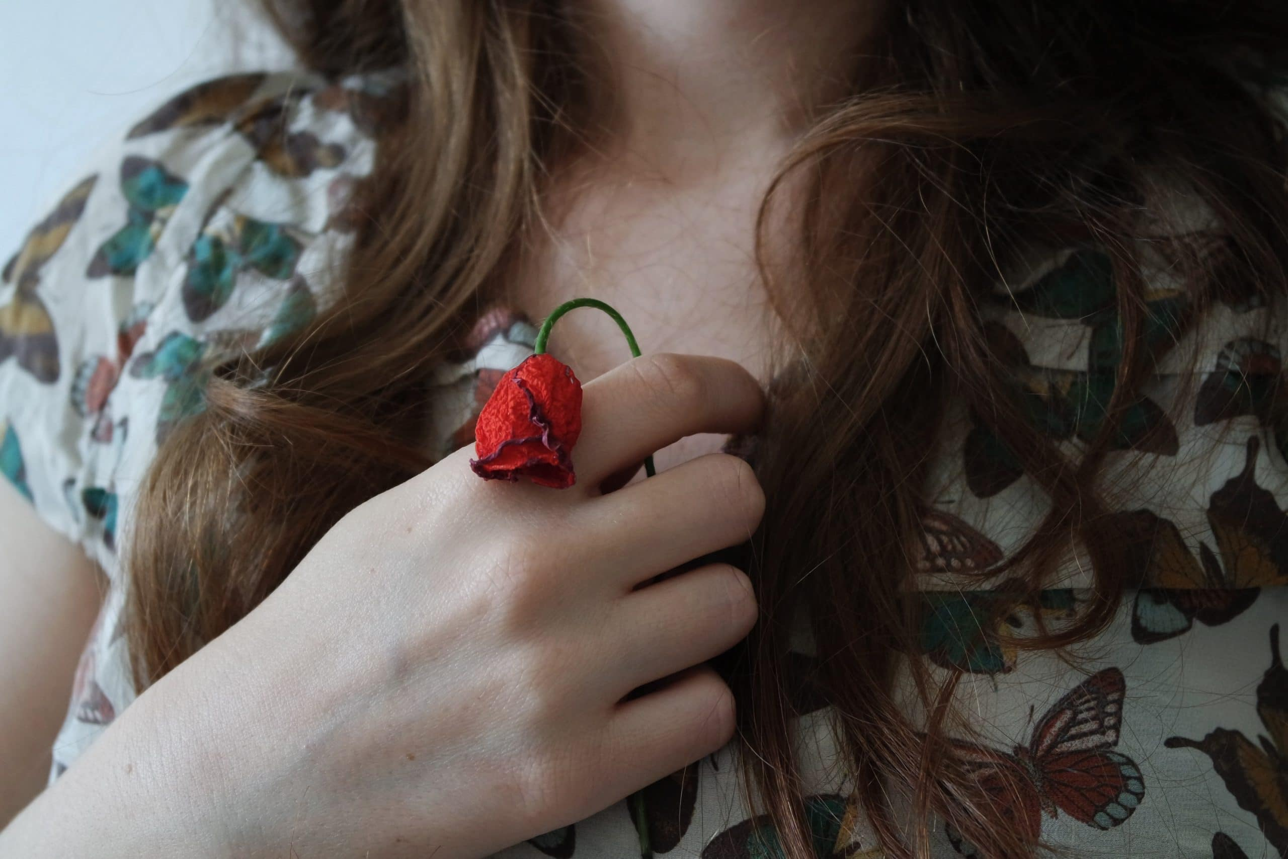 Menina segurando uma rosa caída em seu peito.