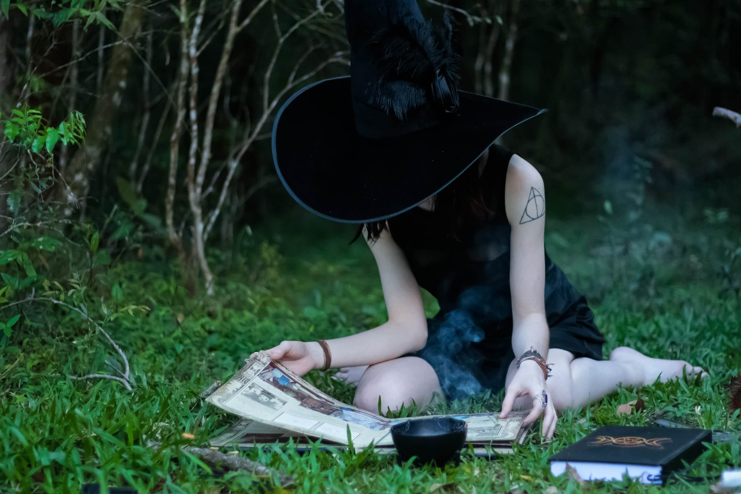 Mulher vestida de bruxa em campo olhando livro