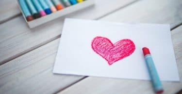 Folha de sulfite branca com um coração vermelho desenhado por giz de cera. Em cima da folha há um giz de cera vermelho. Ambos colocados em cima de uma mesa de madeira, ao lado há uma caixa de giz de cera de diversas cores.
