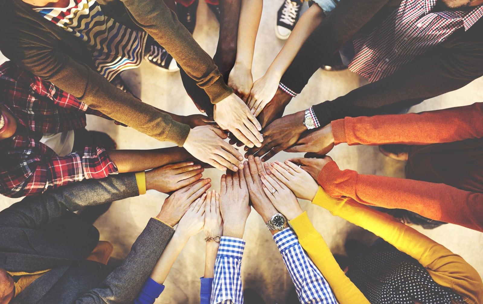 Mãos de um grupo de pessoas juntas.