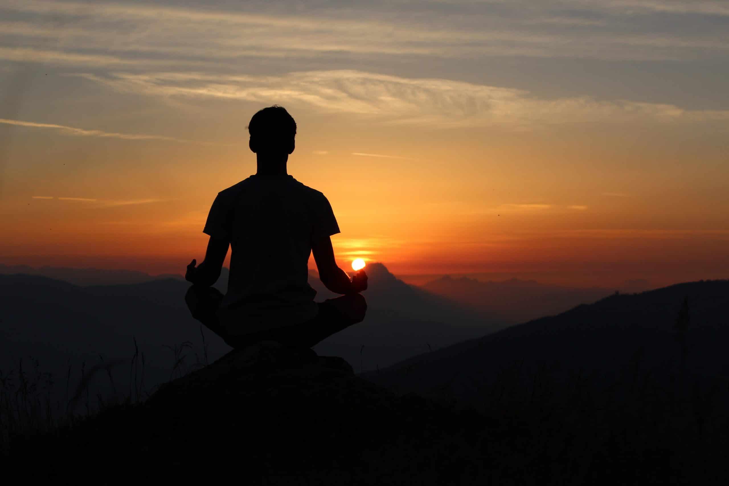 Homem meditando diante do pôr do sol.