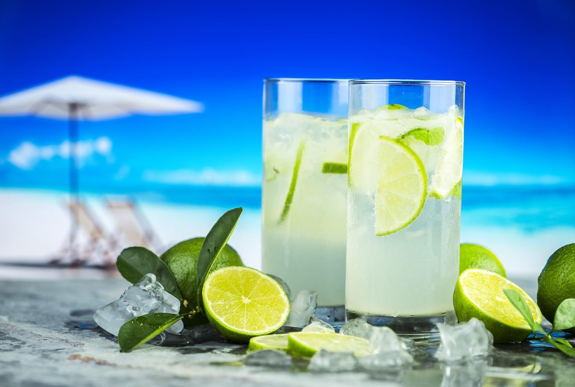 Copos de limonada ao lado de limões pela metade na praia.