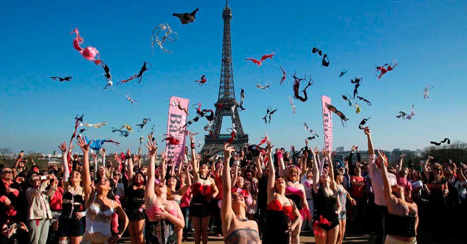 Multidão de mulheres jogando sutiãs para o alto.