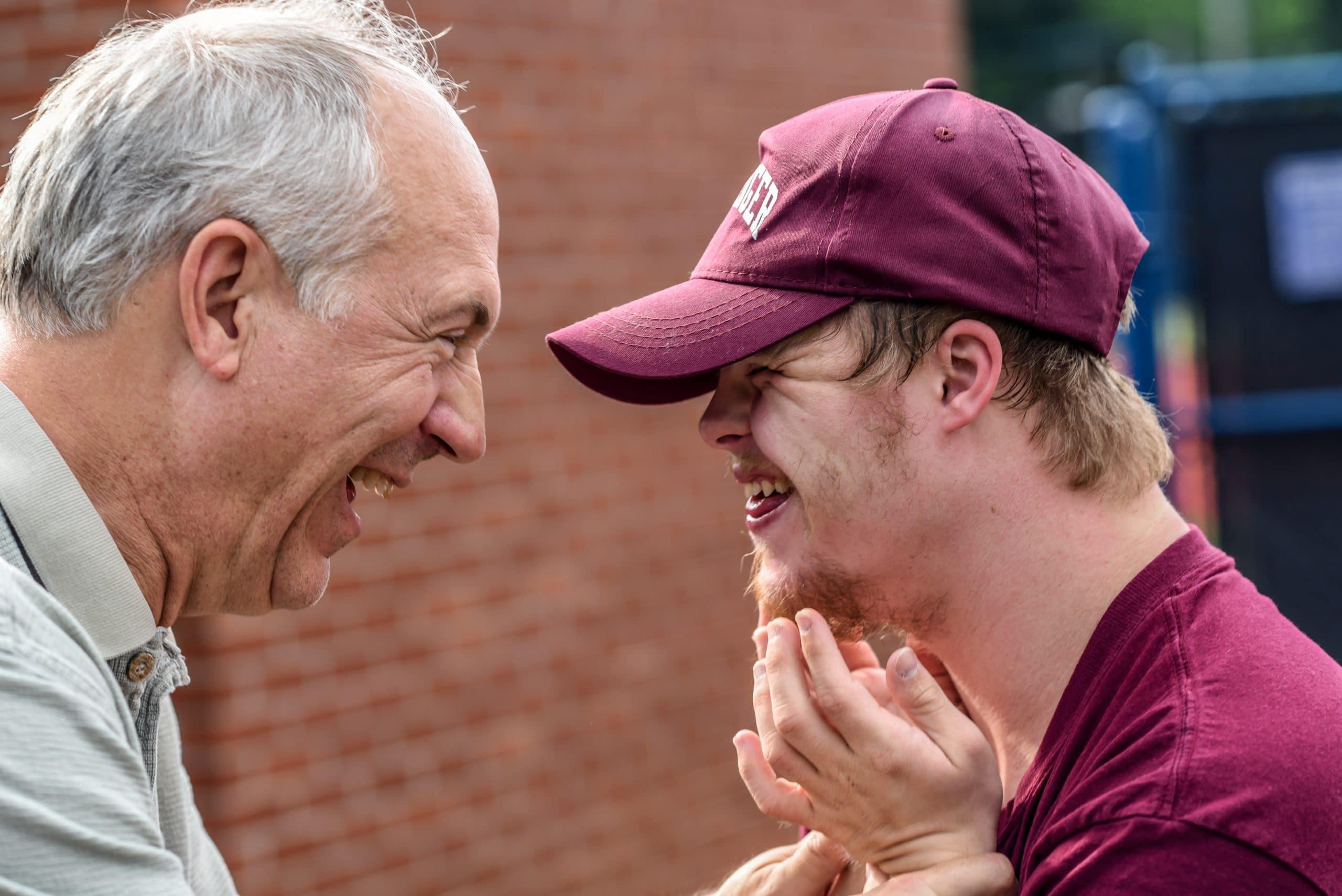 Homem idoso sorrindo para um homem com Síndrome de Down.