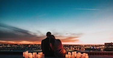 Casal de costas com luzes de velha e céu ao fundo