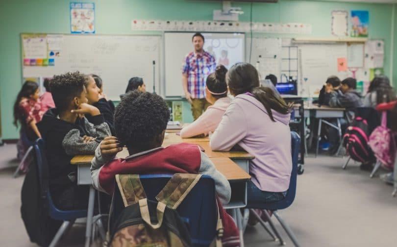 Sala de aula com alunos sentados e professor dando aula